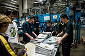 Employees arrange insert sections of the Apple Daily newspaper published by Next Media Ltd at the company's printing facility in the Tseung Kwan O...