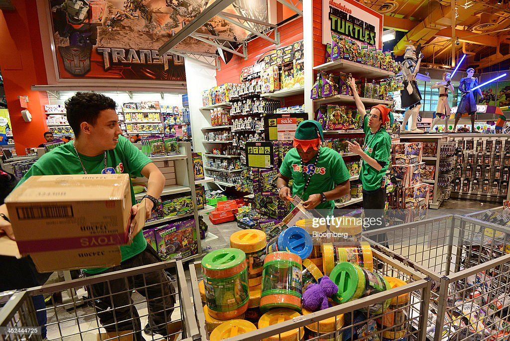 Employees arrange merchandise at a Toys R Us Inc. store ahead of Black Friday in New York, U.S., on Thursday, Nov. 28, 2013. U.S. retailers will kick off holiday shopping earlier than ever this year as stores prepare to sell some discounted items at a loss in a battle for consumers. Photographer: Peter Foley/Bloomberg via Getty Images