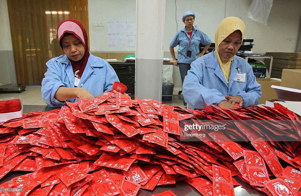 Employees arrange packets of condoms for packaging at the Karex Industries Sdn. Bhd. condom factory in Pontian Besar, Johor, Malaysia, on Thursday, Sept. 20, 2012. Karex Industries' line of business includes the manufacturing of industrial rubber goods, rubberized fabrics, and miscellaneous rubber specialties. Photographer: Goh Seng Chong/Bloomberg via Getty Images