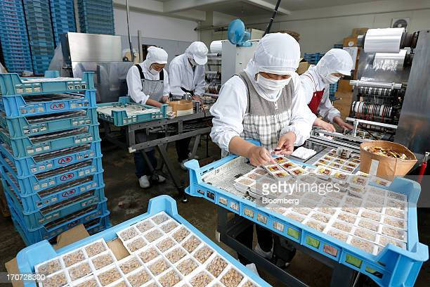 Employees arrange sachets of seasoning sauce and mustard onto polystyrene trays of fermented soybeans known as natto at the Matsushita Shoten YK...
