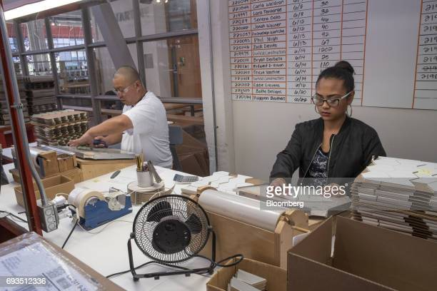 Employees arrange tile pieces into design patterns for shipment at the Heath Ceramics Ltd production facility in San Francisco California US on...