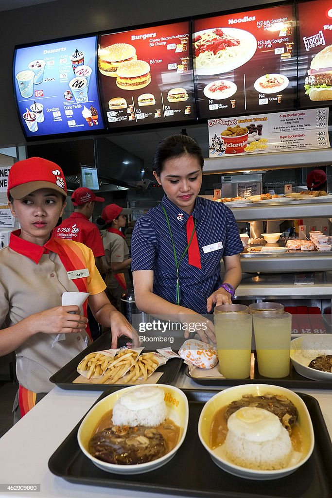 Employees arrange trays of food for customers inside a Jollibee Foods Corp. restaurant in Quezon City, Metro Manila, the Philippines, on Monday, July 28, 2014. Jollibee, which outsells McDonald's Corp. in the Philippines, plans to double earnings in five years as it accelerates its expansion in China and seeks an acquisition in the U.S. Photographer: Veejay Villafranca/Bloomberg via Getty Images