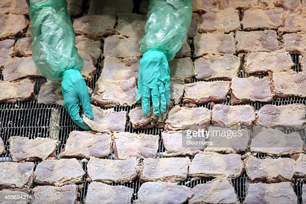 Employees arrange uncooked crumbed chicken pieces as they move along a conveyor in the precooked and frozen meat section at the Charoen Pokphand...