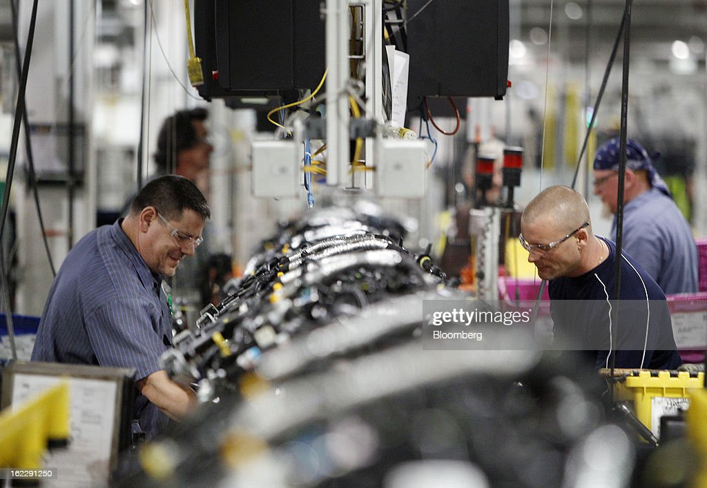 Employees assemble 2.0 liter ecoboost engines on the production line at the Ford Motor Co. Cleveland Engine Plant in Brook Park, Ohio, U.S., on Thursday, Feb. 21, 2013. Ford Motor Co. said it will invest $200 million to make four-cylinder engines at the plant starting in late 2014 as the second-largest U.S. automaker equips an increasing number of models with smaller, more fuel-efficient powertrains. Photographer: David Maxwell/Bloomberg via Getty Images