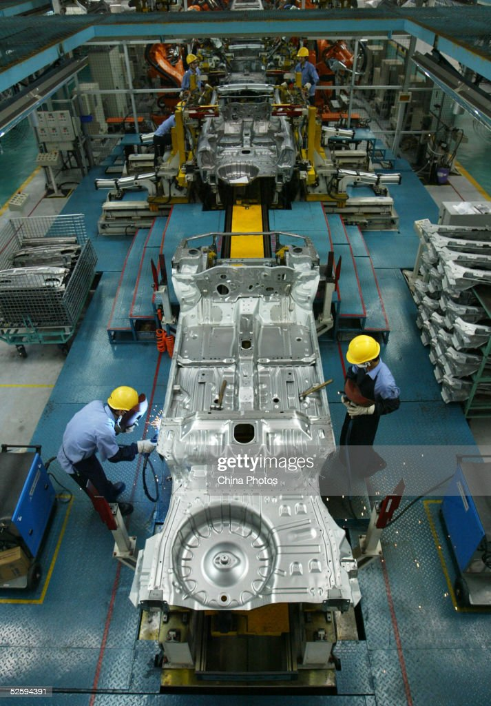 Employees assemble a cars in Mazda's 'Family' line of vehicles at China First Automobile Works (FAW) Group Haima Automobile Co., Ltd. April 6, 2005 in Haikou, Hainan Province, China. China has become the world's third largest automotive market with 2004 car sales in the country growing 15.17 percent to 2.33 million units, even though curbs on credit reduced demand. The market began slowing by mid-2004, affected by the government's measures to cool a fast-expanding economy. Analysts expect car sales in China to increase in 2005 by 10 percent.