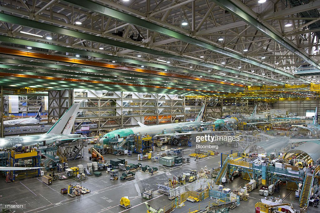 Employees assemble Boeing Co. 777 airplanes on a moving production line at the company's facility in Everett, Washington, U.S., on Tuesday, June 25, 2013. Boeing Co. uses the Automated Spray Method (ASM), which consists of a robot with two guns that applies two paints at different thicknesses, to efficiently paint the wings of the popular 777 airplanes. Photographer: Mike Kane/Bloomberg via Getty Images