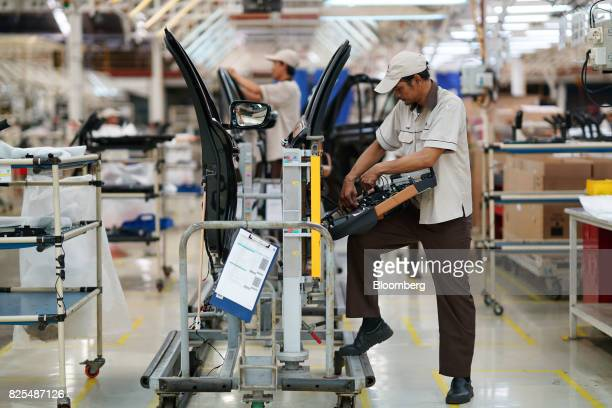 Employees assemble door panels for the BMW 530i sedan on the production line at a PT Gaya Motor plant in Jakarta Indonesia on Wednesday Aug 2 2017...