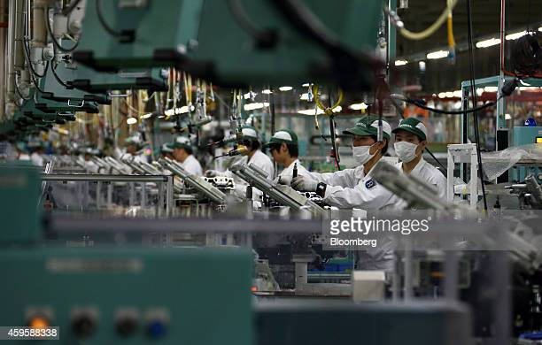 Employees assemble Honda Motor Co motorcycle engines on the production line during a tour of the company's Kumamoto factory in Ozu Kumamoto...