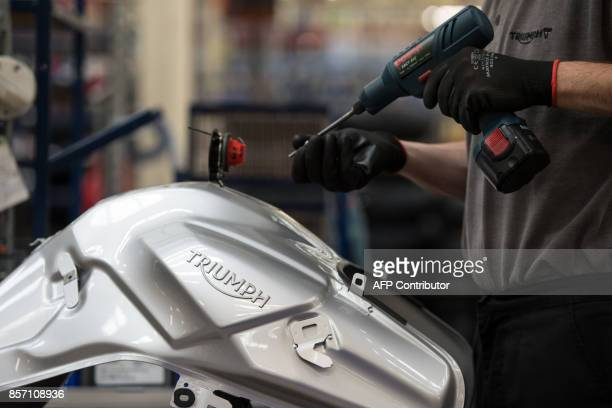 Employees assemble motorcycles on the assembly line at the Triumph Motorcycles factory in Hinckley central England on October 2 2017 Triumph which...
