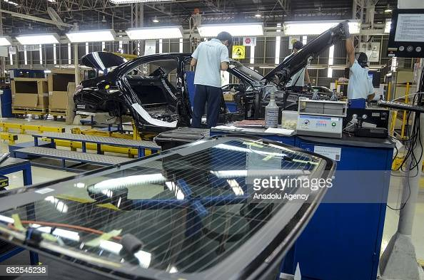 Employees assemble parts of a MercedesBenz EClass vehicle on the production line of a MercedesBenz factory in Bogor Indonesia on January 24 2017...