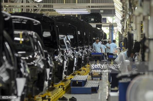 Employees assemble parts of MercedesBenz EClass vehicles on the production line of a MercedesBenz factory in Bogor Indonesia on January 24 2017...