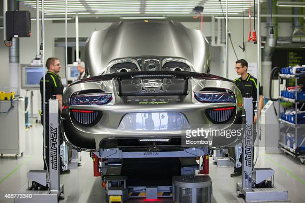 Employees assemble Porsche AG 918 Spyder Ehybrid automobiles as they move along the production line at the Porsche AG factory in Stuttgart Germany on...