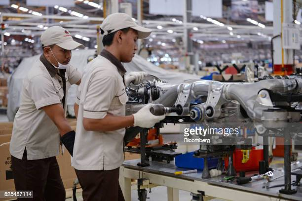 Employees assemble the drivetrain of a BMW 530i sedan on the production line at a PT Gaya Motor plant in Jakarta Indonesia on Wednesday Aug 2 2017...