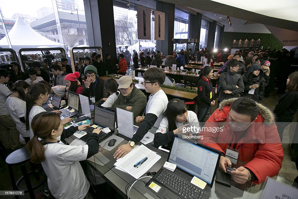 Employees assist customers as they purchase Apple Inc. iPhone 5 smartphones at a KT Corp. Olleh brand mobile phone store in Seoul, South Korea, on Friday, Dec. 7, 2012. The iPhone 5 went on sale in South Korea today. Photographer: Jean Chung/Bloomberg via Getty Images