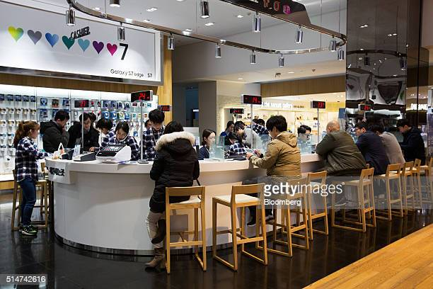 Employees assist customers at a Samsung Electronics Co D'light flagship store in Seoul South Korea on Friday March 11 2016 Samsung's latest Galaxy S7...