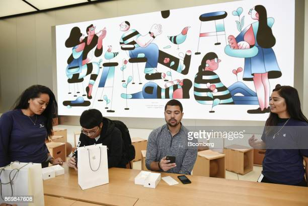 Employees assist customers with Apple Inc iPhone X smartphones during the sales launch at a store in San Francisco California US on Friday Nov 3 2017...