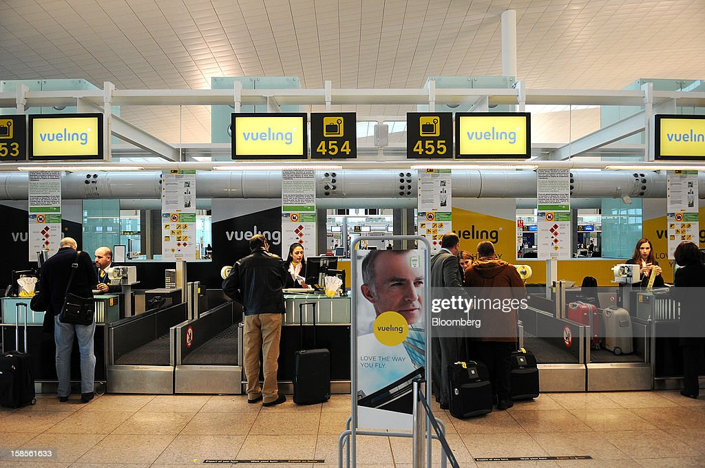 Employees assist passengers checking in their luggage at the Vueling Airlines SA check-in desk at EL Prat airport in Barcelona, Spain, on Wednesday, Dec. 19, 2012. International Consolidated Airlines Group SA won't require European Union approval to buy 100 percent of low-cost carrier Vueling Airlines SA, the EU's antitrust chief said. Photographer: Stefano Buonamici/Bloomberg via Getty Images