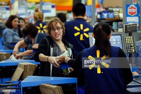 Employees assist shoppers at the check out counter of a WalMart Stores Inc location ahead of Black Friday in Los Angeles California US on Monday...