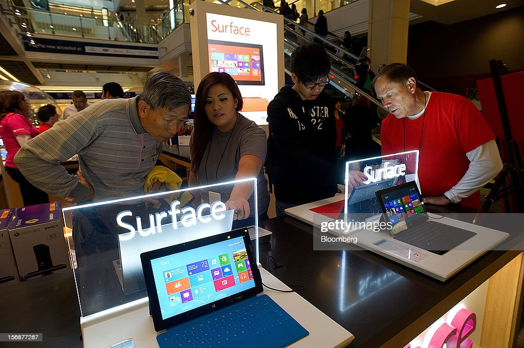 Employees assist shoppers with the Microsoft Corp. Surface tablet computer at a pop-up store in the Westfield San Francisco Centre in San Francisco, California, U.S., on Friday, Nov. 23, 2012. To get shoppers to spend more than last year, retailers have continued to turn Black Friday, originally a one-day event after Thanksgiving, into a week's worth of deals and discounts. Photographer: David Paul Morris/Bloomberg via Getty Images