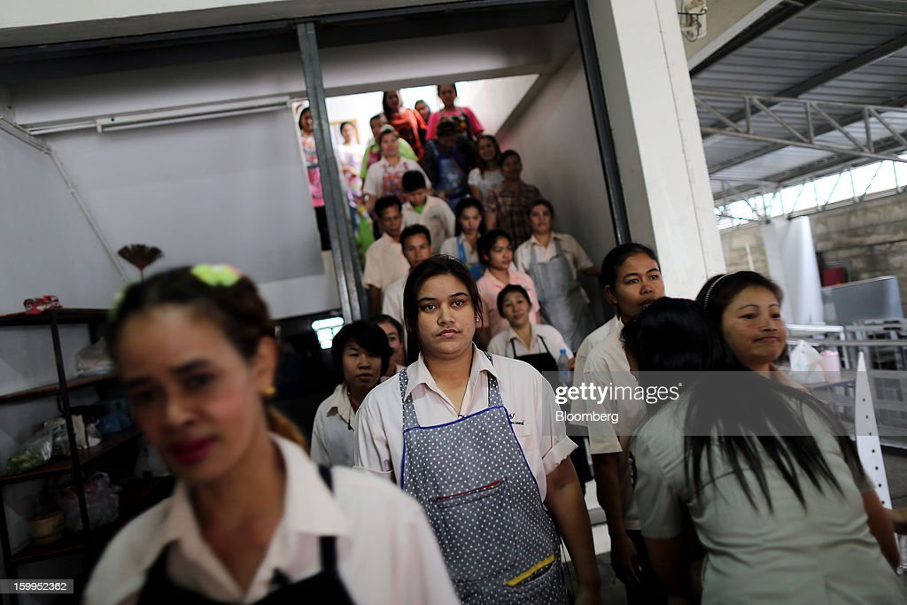 Employees at a BJ Jeans factory are searched by a security guard, second right, as they leave for their lunch break in Bangkok, Thailand, on Wednesday, Jan. 23, 2013. Prime Minister Yingluck Shinawatra's government last month approved a new round of increases in the daily minimum wage to 300 baht ($9.8) from the beginning of this year, after a similar raise in April in seven provinces including Bangkok. Photographer: Dario Pignatelli/Bloomberg via Getty Images