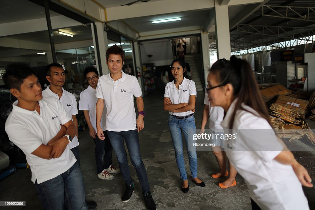 Employees at a BJ Jeans factory chat during their lunch break in Bangkok, Thailand, on Wednesday, Jan. 23, 2013. Prime Minister Yingluck Shinawatra's government last month approved a new round of increases in the daily minimum wage to 300 baht ($9.8) from the beginning of this year, after a similar raise in April in seven provinces including Bangkok. Photographer: Dario Pignatelli/Bloomberg via Getty Images