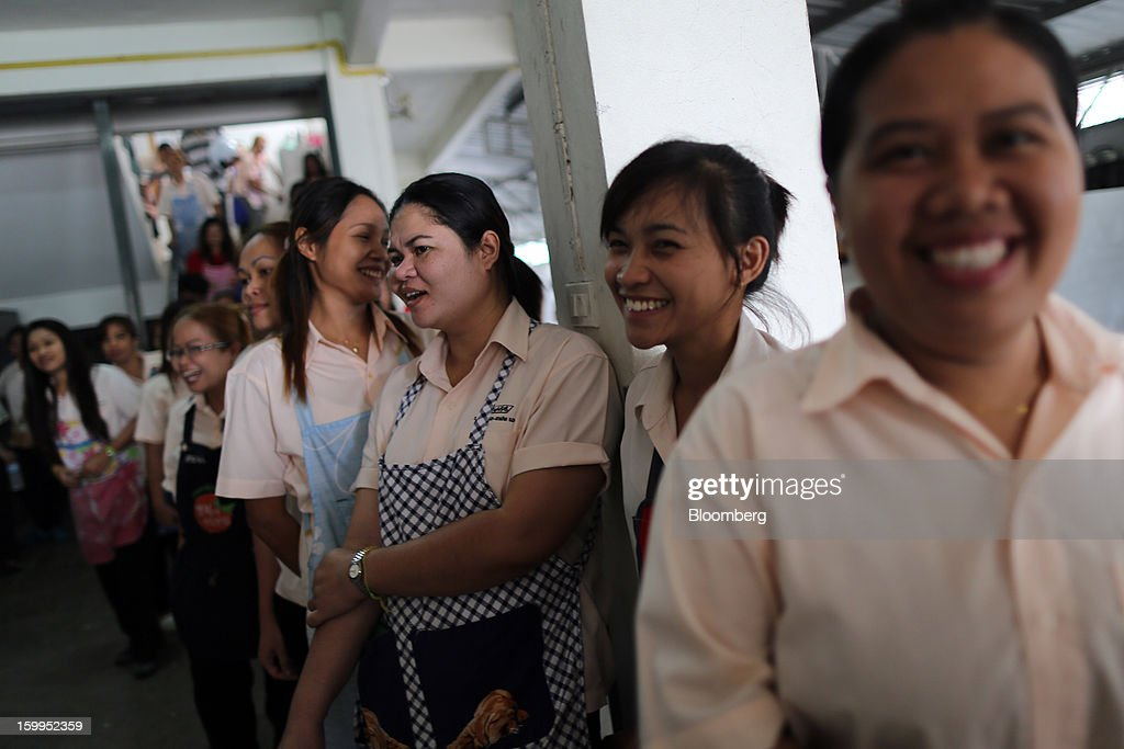 Employees at a BJ Jeans factory leave for their lunch break in Bangkok, Thailand, on Wednesday, Jan. 23, 2013. Prime Minister Yingluck Shinawatra's government last month approved a new round of increases in the daily minimum wage to 300 baht ($9.8) from the beginning of this year, after a similar raise in April in seven provinces including Bangkok. Photographer: Dario Pignatelli/Bloomberg via Getty Images