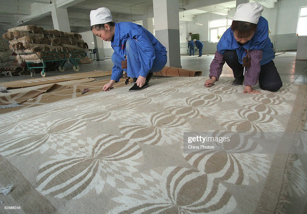 Employees at a Qinghai Tibetan Sheep Carpets (Group) Ltd. factory work in the final stages of producing a carpet April 4, 2005 in Xining, Qinghai Province, northwest China. Qinghai Tibetan Sheep Carpets is a famous import and export enterprise in China's west region, with its traditional Tibetan carpets exported to more than 24 countries and regions in Europe, Asia and the U.S. The Chinese government is seeking ways to boost development of the west region, as economic growth of eight percent has been forcast for this year.