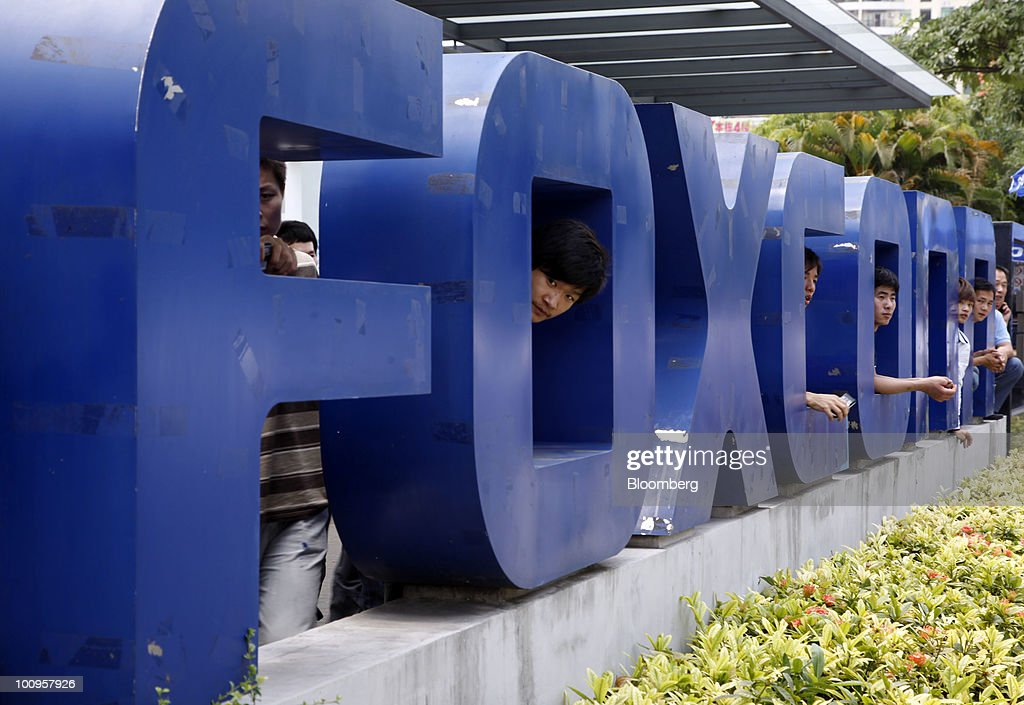 Employees at Hon Hai's Foxconn plant peek out from the back of a company sign in Shenzhen, China, on Wednesday, May 26, 2010. Apple Inc., Hewlett-Packard Co. and Dell Inc. said they're investigating working conditions at Taiwan's Hon Hai Group after a mounting number of suicides at their contract manufacturer. Photographer: Qilai Shen/Bloomberg via Getty Images