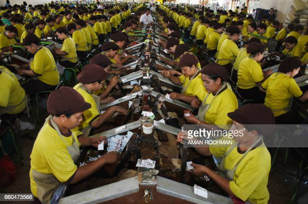 TOPSHOT Employees at PT Gandum a local company that produces cigarettes work at a factory in Malang on March 30 2017 / AFP PHOTO / AMAN ROCHMAN