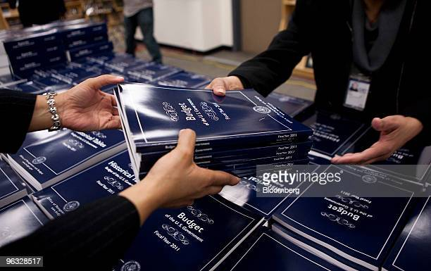 Employees at the US Government Printing Office deliver copies of the proposed 2011 fiscal year budget for members of the media in Washington DC US on...