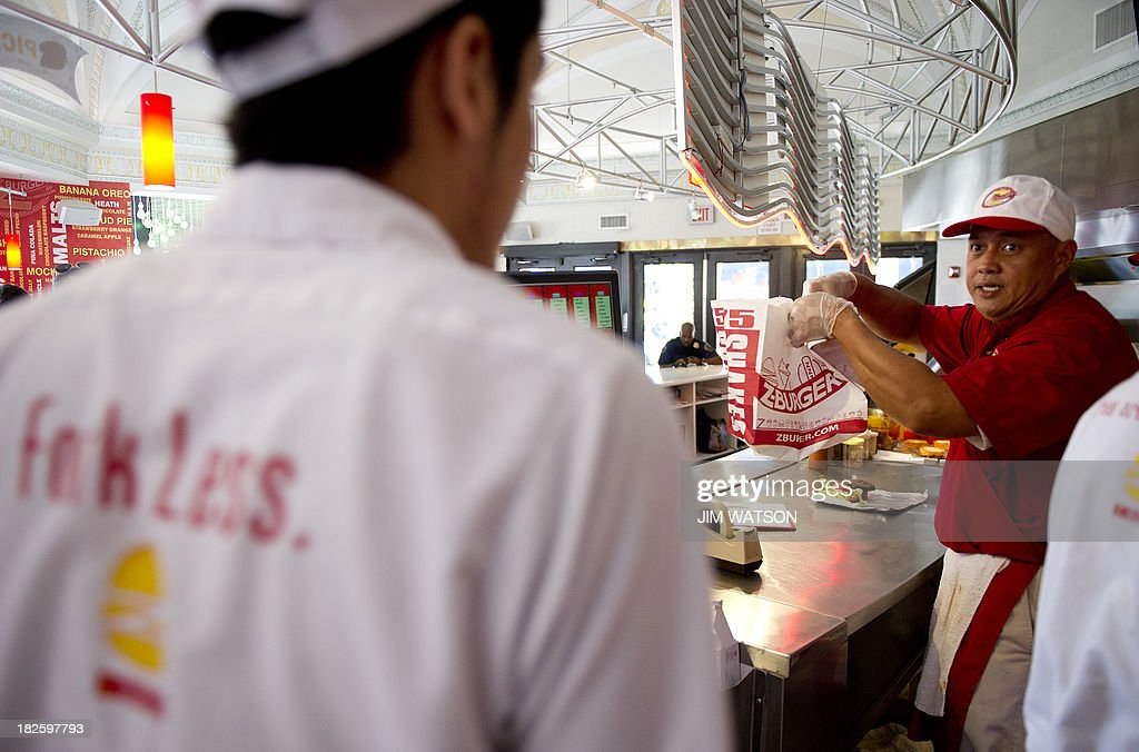 Employees at Z-Burger in Washington, DC, prepare food during the lunch hour rush October 1, 2013. The fast-food chain is promising free hamburgers to federal workers who find themselves furloughed after the US government shutsdown Tuesday, its founder and proprietor Peter Tabibian said. AFP PHOTO/Jim WATSON