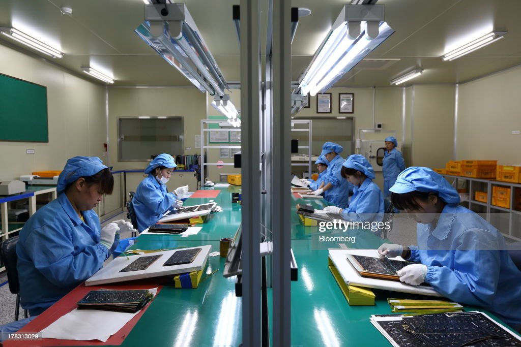 Employees attach protective film to Flexible Printed Circuit Board (F-PCB) panels on the production line at the Seil Electronics Co. factory in Incheon, South Korea, on Wednesday, Aug. 28, 2013. South Korea has surpassed Brazil, Russia and India to become the second-biggest emerging stock market for the first time since 2006, as a stable won and record current-account surplus lure investors. Photographer: SeongJoon Cho/Bloomberg via Getty Images