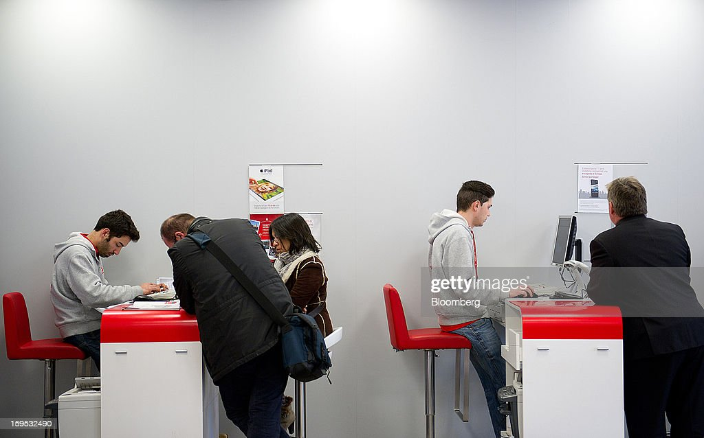 Employees attend customers at service counters inside a Vodafone Group Plc store in Barcelona, Spain, on Tuesday, Jan. 15, 2013. Vodafone Group Plc, the world's second largest mobile-phone company, plans to reduce the workforce at its Spanish unit as unemployment exceeding 25 percent in the recession-plagued country causes sales to drop. Photographer: David Ramos/Bloomberg via Getty Images