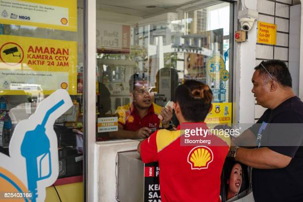 Employees attend to a customer at a Royal Dutch Shell Plc gas station in Kota Kinabalu in Sabah Malaysia on Sunday July 30 2017 Sabah and neighboring...