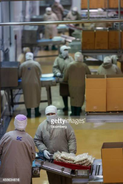 Employees box bags of crumbed chicken pieces in the packaging section at the Charoen Pokphand Foods Pcl processing plant in Chok Chai Nakhon...