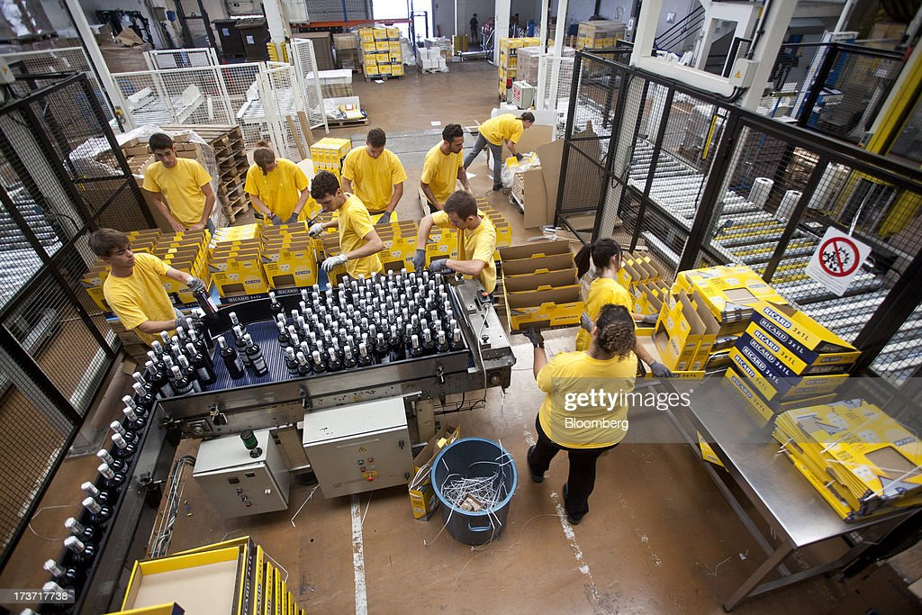 Employees box bottles of Ricard pastis, produced by Pernod Ricard SA, as they reach the end of an automated production line at the company's plant in Bordeaux, France, on Tuesday, July 16, 2013. Distillers such as Diageo and Pernod Ricard SA are seeking to expand in emerging markets where booming economic growth is creating a burgeoning middle class with more disposable income. Photographer: Balint Porneczi/Bloomberg via Getty Images