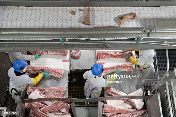 Employees butcher pork ribs as trotters mover along an overhead conveyor at a Smithfield Foods Inc pork processing facility in Milan Missouri US on...