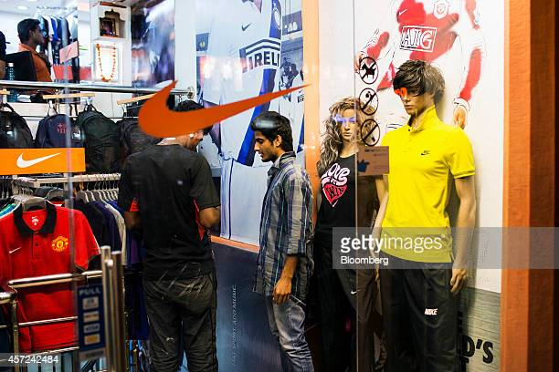 Employees chat inside a Nike Inc store on Mirza Ismail Road in Jaipur Rajasthan India on Monday Oct 13 2014 Indias retail inflation slowed more than...