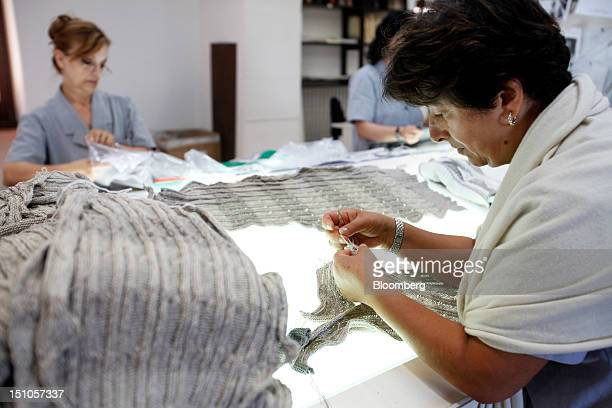 Employees check garments during the quality control process at the Brunello Cucinelli SpA production facility in Solomeo near Perugia Italy on...