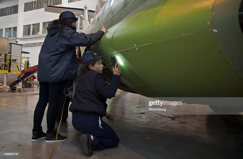 Employees check the fuselage of an ATR-72 turboprop aircraft, manufactured by Avions de Transport Regional (ATR), during assembly at the company's production facility in Colomiers, France, on Wednesday, Jan. 23, 2013. ATR, the world's largest maker of turbo-propeller airliners, reported record profit for 2012, even as it fell short of its shipment target amid production delays. Photographer: Balint Porneczi/Bloomberg via Getty Images