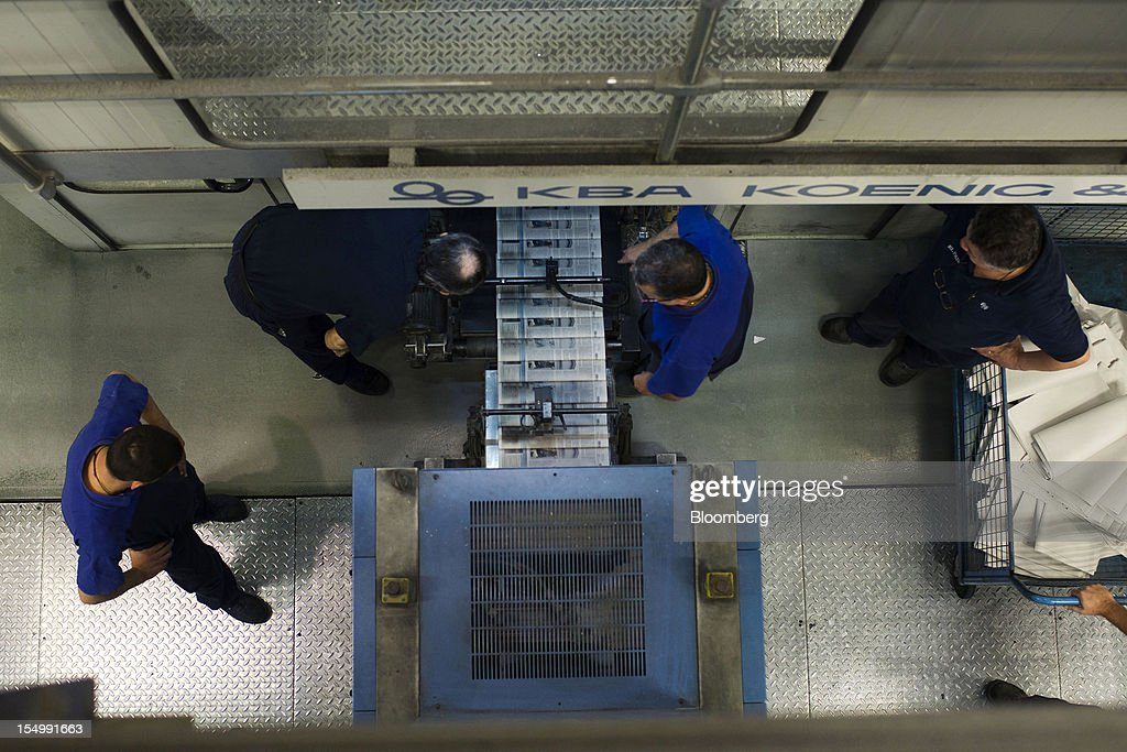 Employees check the print quality of El Pais newspaper pages as they roll off the printing presses at the El Pais printing plant in Madrid, Spain, on Tuesday, Oct. 30, 2012. Prisa, the publisher of El Pais newspaper, has announced staff reductions and salary cuts. Photographer: Angel Navarrete/Bloomberg via Getty Images