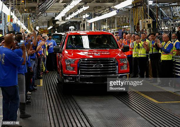 Employees cheer as the first 2015 Ford Motor Co F150 truck rolls off the production line during an event at the company's Dearborn Truck Assembly...