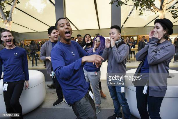 Employees cheer before customers are let in to purchase the Apple Inc iPhone X smartphone during the sales launch at a store in San Francisco...