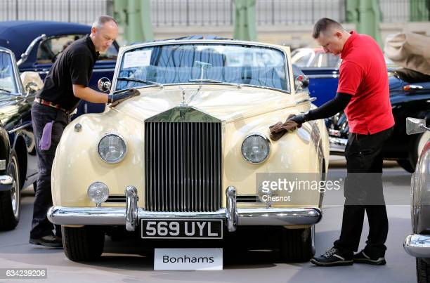 Employees clean a RollsRoyce model during a press preview before a mass auction of vintage vehicles organised by Bonhams auction house at the Grand...