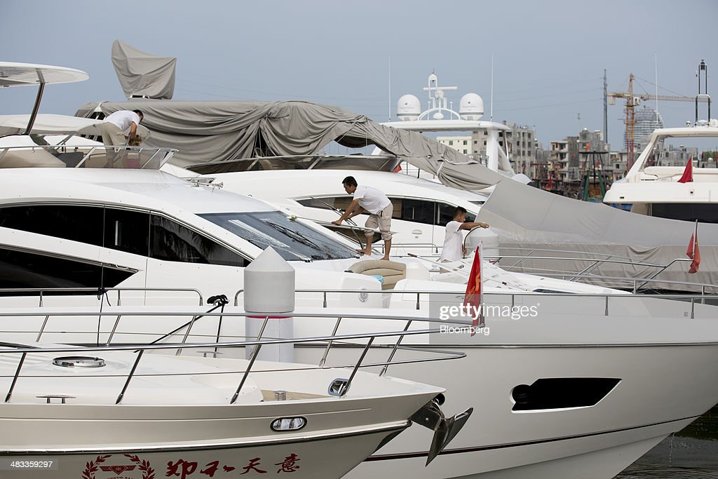 Employees clean a yacht at the Visun Royal Yacht Club in the Sanya Bay district of Sanya, Hainan Province, China, on Monday, April 7, 2014. The yuan is poised to recover from declines that have made it Asia's worst-performing currency as China seeks to prevent an exodus of capital that would threaten economic growth, according to the most accurate forecasters. Photographer: Brent Lewin/Bloomberg via Getty Images