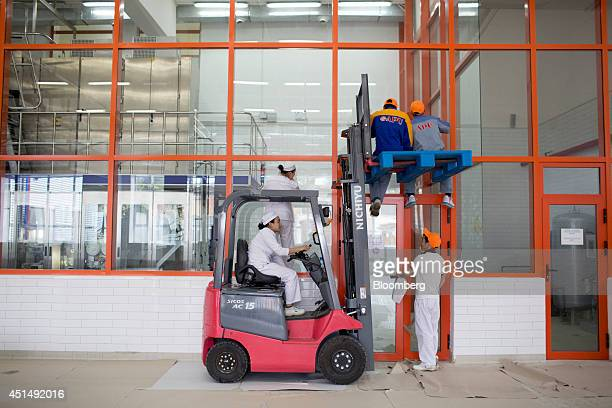 Employees clean windows at the APU JSC dairy plant in Ulaanbaatar Mongolia on Tuesday June 24 2014 APU is Mongolia's largest spirit and beverage...
