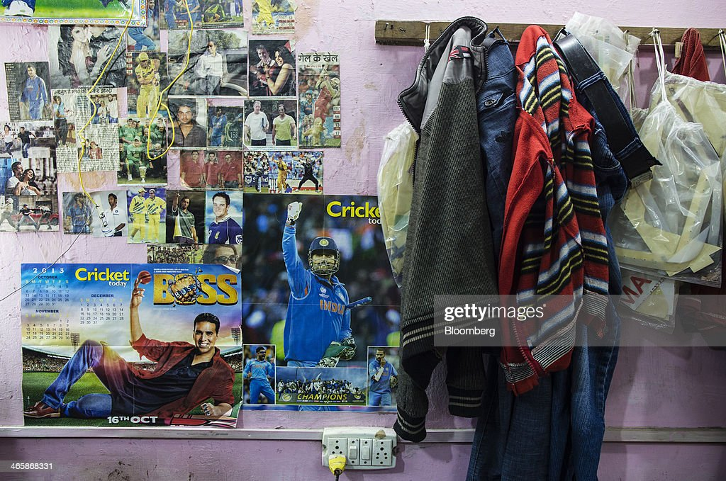Employees' clothes hang next to cricket posters at a Stanford Cricket Industries factory in Meerut, Uttar Pradesh, India, on Wednesday, Jan. 29, 2014. The Indian Premier League (IPL), the worlds richest cricket competition, auction for IPL 2014 is scheduled to begin on Feb. 12 with the seasons first match to be played on April 8. Photographer: Prashanth Vishwanathan/Bloomberg via Getty Images