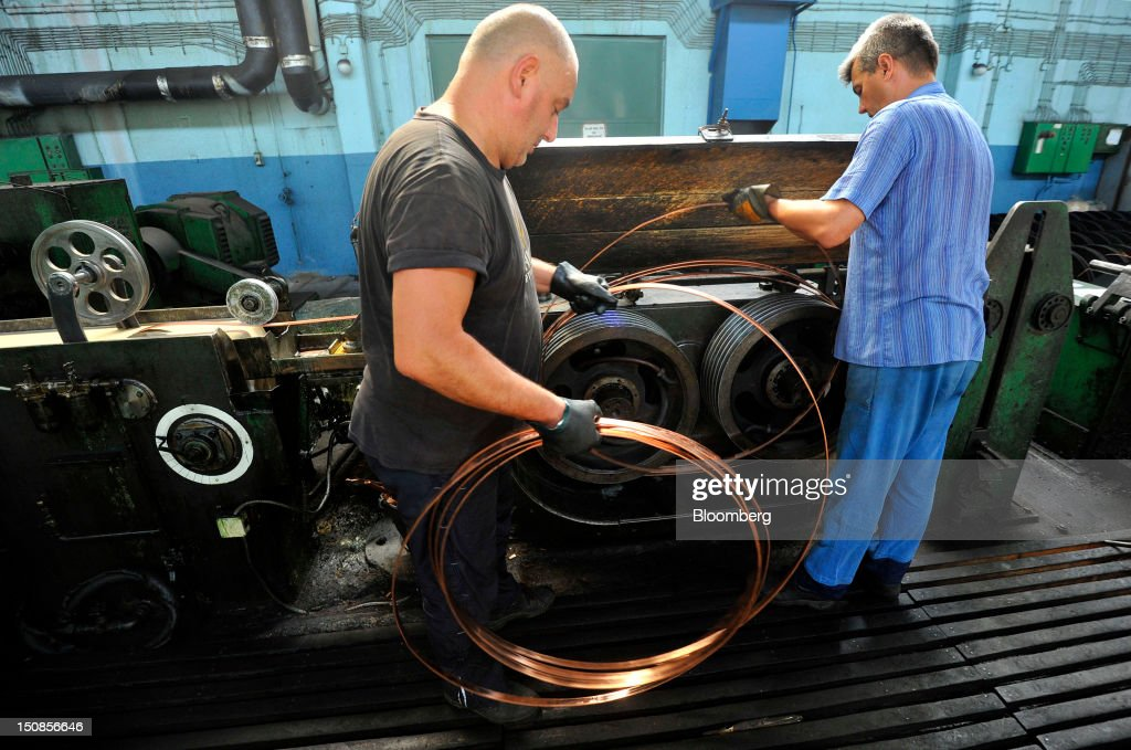 Employees collect copper wire as it rolls off a machine at the copper mining and smelting complex, operated by RTB Bor Group, in Bor, Serbia, on Friday, Aug. 24, 2012. Copper neared a one-week low in London on signs Asian economies are slowing and speculation that U.S. policy makers will refrain from a fresh round of stimulus. Photographer: Oliver Bunic/Bloomberg via Getty Images