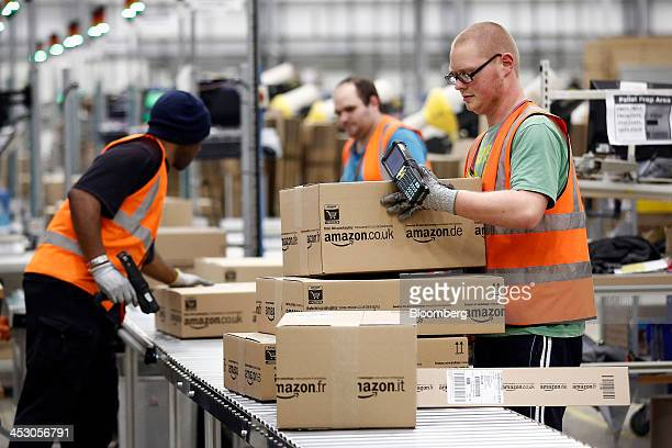 Employees collect packaged customer orders from a conveyor belt ahead of shipping at one of Amazoncom Inc's fulfillment centers in Rugeley UK on...