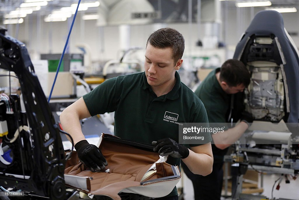 Employees cover seat frames with leather inside the Bentley Motors Ltd. workshop in Crewe, U.K., on Thursday, Nov. 29, 2012. Consumer spending and exports propelled the U.K. economy to its fastest growth since 2007 in the third quarter as the Olympics and a post-Jubilee rebound saw household expenditure rise the most in more than two years. Photographer: Simon Dawson/Bloomberg via Getty Images